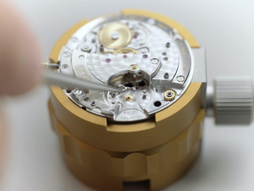 Une fois les composants nettoyés et séchés, l'horloger réassemble le mouvement. Ici, la pose de l'ancre.